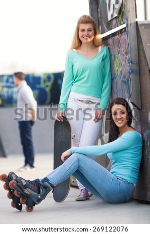 Two teenage skater girls hanging out in a skateboard park - stock photo