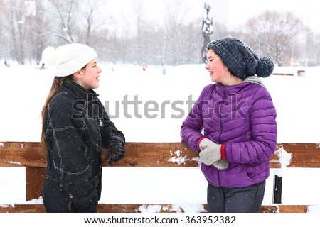 two teenager girl in knitted woolen hat and down overall and jacket on the skating ring talk on smile on the snowy white background - stock photo