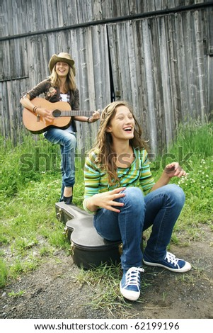 Two teenager girl playing guitar and having fun