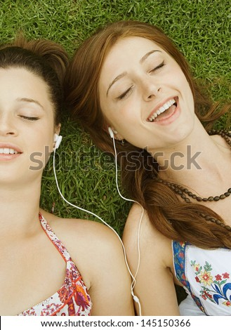 Two teenager girls relaxing with their heads together laying down on green grass in a park, sharing their headphones and singing to the music, having fun and enjoying the song. - stock photo