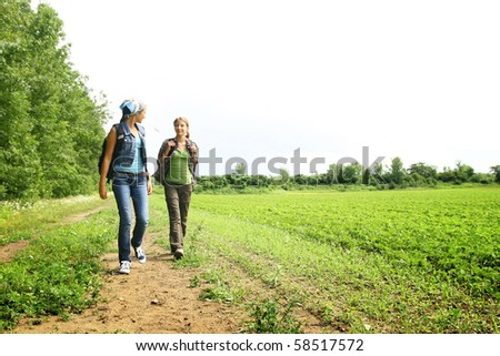 Two teenager girls walking in a path on a mountain