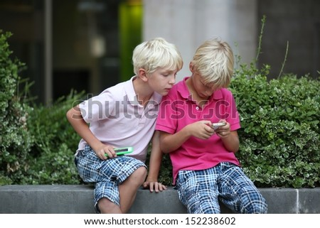 Two teenager kids, twin brothers, are playing together games with touchscreen smart phones sitting on a bench outdoors - stock photo