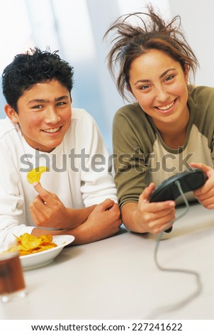 Two teenager on the floor playing with computer game - stock photo