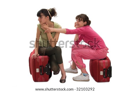 Two teenager sitting on huge luggage looking at surrounding, one girl point at something - stock photo