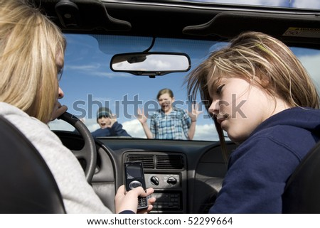 Two teenagers being distracted by a cell phone text, instead of watching the road.  They are about to hit a boy and girl crossing infront of the car. - stock photo