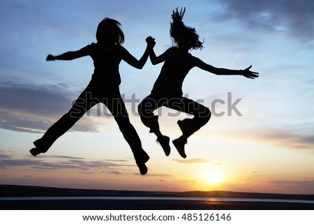 Two teenagers having fun and jumping on the beach at sunset. Silhouette.