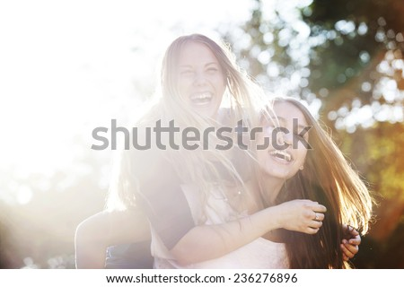 Two teenagers laughing in the park - stock photo