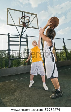 Two teenagers playing basketball at the street playground - stock photo