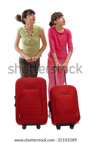 Two teenagers push huge luggage and looking at surroundings - stock photo