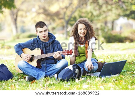 Two teenagers resting in the park and listen music from a guitar  - stock photo