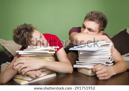 Two teenagers sleeping on books, tired from schoolwork (laziness)