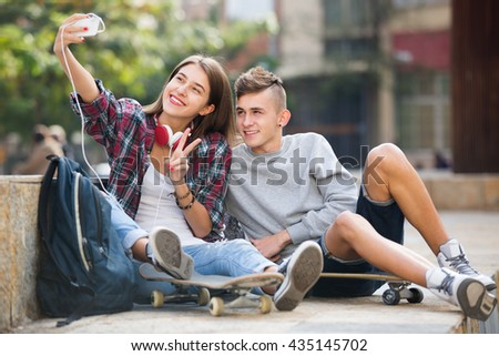 Two teenagers smiling and doing selfie together on smartphone outdoors  - stock photo
