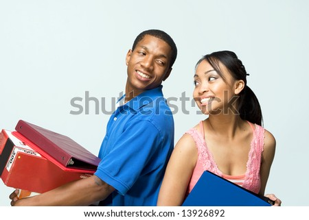 Two teenagers standing back to back holding notebooks are smiling as they look at each other. Horizontally framed photograph