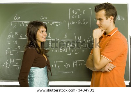 Two teenagers standing in front of blackboard. One smiling girl and thinking boy. Side view