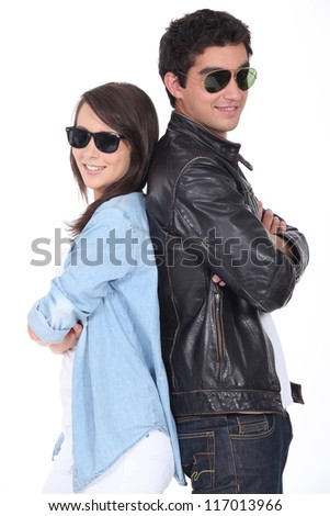 Two teenagers stood back to back wearing sunglasses - stock photo