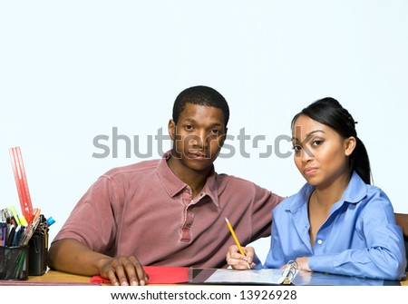 Two Teens are are seated at a desk taking notes and looking serious. There are pencils, folders, and paper on the desk. Horizontally framed photograph - stock photo