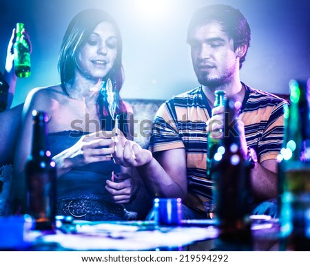 two teens at party passing marijuana joint - stock photo