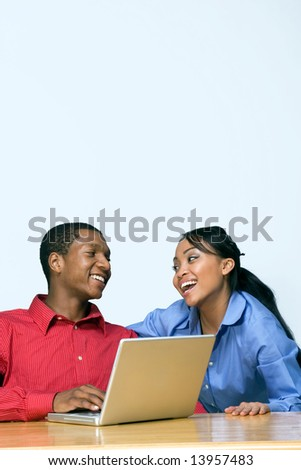 Two Teens looking at each other and laughing as he types on a Laptop Computer. Horizontally framed photograph - stock photo