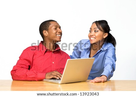Two Teens looking at each other and smiling as he types on a Laptop Computer. Horizontally framed photograph - stock photo