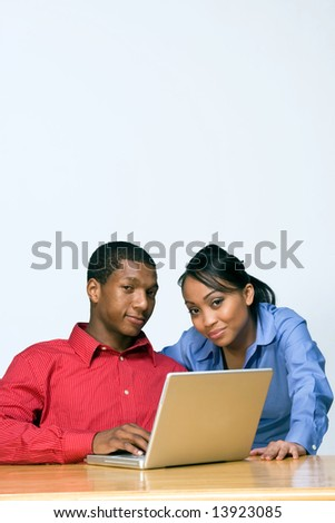 Two Teens looking serious as they stare ahead and he holds a Laptop Computer. Vertically framed photograph
