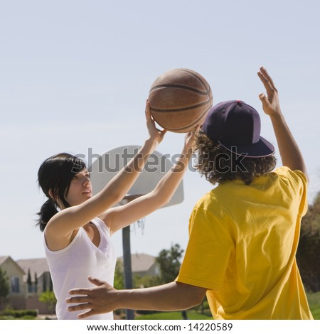 Two teens play basketball at a park