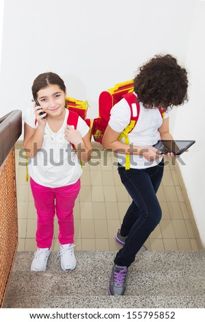Two ten year old schoolgirl using computer tablet and smart phone - stock photo