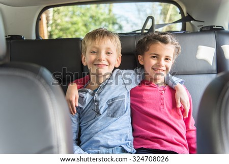 Two ten years old are sitting at the back of a car They are looking at camera, smiling arms in arms like friends or brother and sister The blond boy is wearing a blue shirt and the girl a pink top