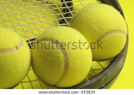 two tennis rackets and three balls on yellow diagonal - stock photo