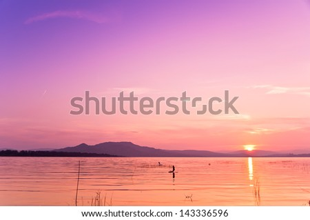 Two tents jumping on the water in calmness in a coloring summer late afternoon - stock photo