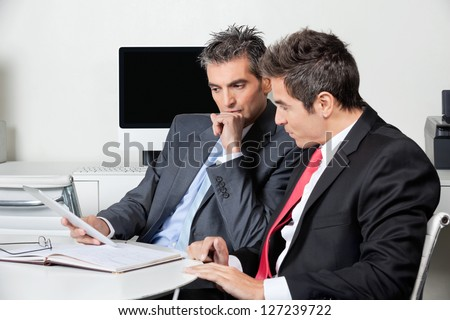 Two thoughtful businessmen using digital tablet at desk in office - stock photo