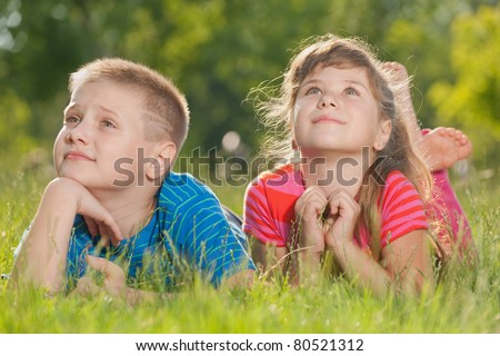Two thoughtful children are lying on the grass