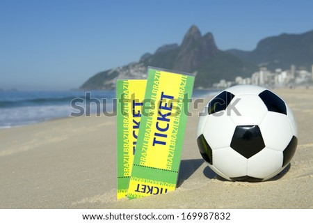Two tickets to football event in sand with soccer ball on Ipanema Beach Rio de Janeiro Brazil - stock photo
