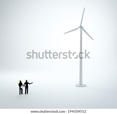 Two tiny engineers building a wind power plant  - stock photo
