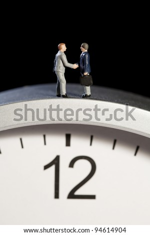 Two tiny model figures of businessmen shaking hands on top of a clock showing the time as five minutes to twelve, vertical. - stock photo