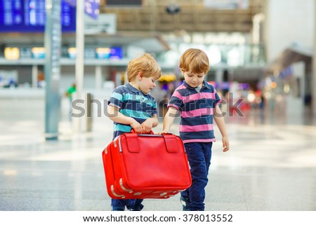 Two tired little sibling kids boys at the airport, traveling together. Angry family, twins children waiting. Canceled flight due to pilot strike.