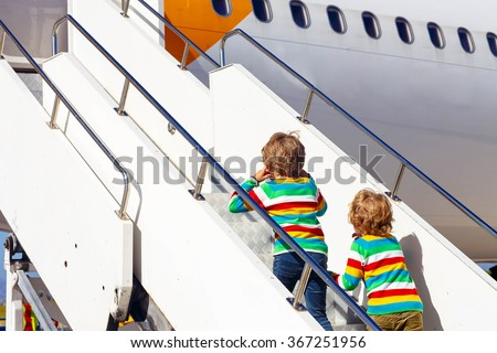 Two tired little sibling kids boys at the airport, traveling together. Upset children climbing stairs on plane. Canceled flight due to pilot strike. - stock photo