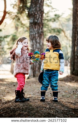 two toddler friends having fun and playing on the walk in spring forest - stock photo