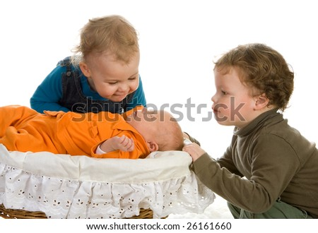 Two toddlers admiring their newborn little sister - stock photo