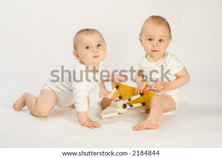 Two toddling boys in white bodysuits with wooden horse
