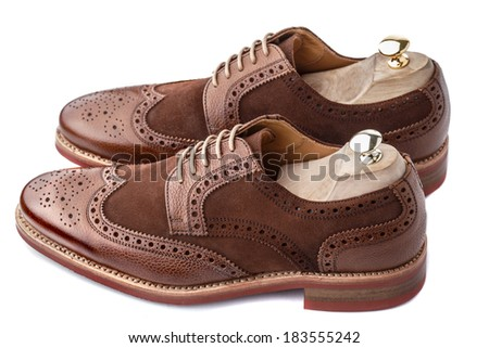 Two tone men brogues with shoe trees inserted. The upper is stunning combination of brown calf with brown suede. - stock photo