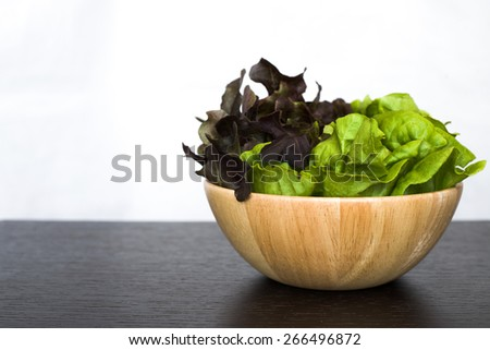 Two (2) tone salad in wooden bamboo bowl on dark wood table isolated on white background - stock photo