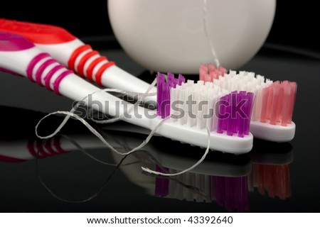 Two toothbrushes and dental floss - common toiletries - stock photo