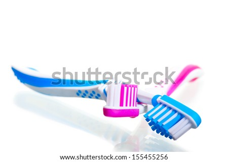 two toothbrushes crossed on a white background