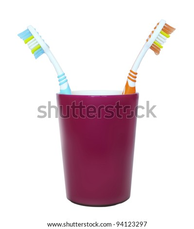 two toothbrushes facing each other in a glass isolated photo