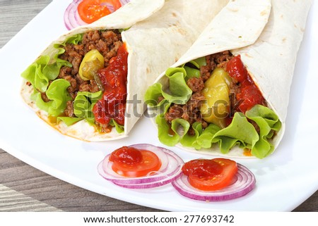 Two tortilla with meat and vegetable on the plate