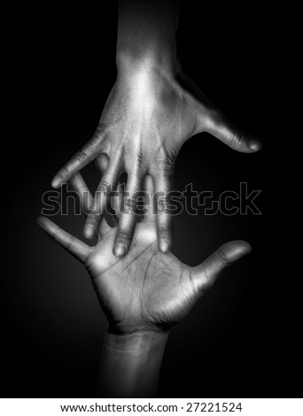 Two touching human hands in black and white - stock photo