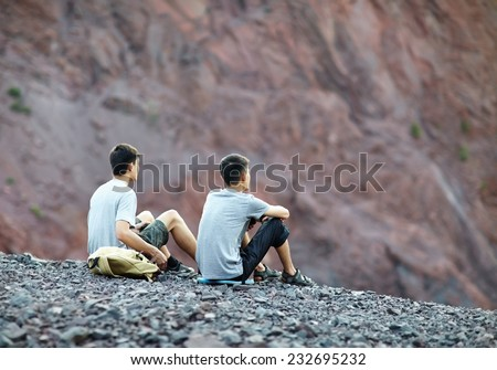 Two tourist young men sitting on rocky cliff and enjoying view - stock photo