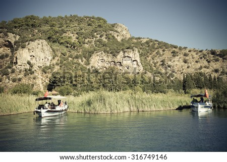 Two touristic boats on the background of Lycian Tombs of ancient Caunos city, Dalyan, Turkey. Toned. - stock photo