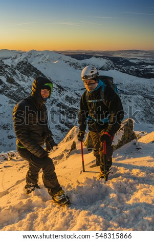 Two tourists in the winter at sunset in the mountains.