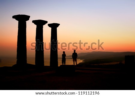 Two Tourists Watching The Sunset At The Athena Temple; Canakkale, Turkey